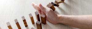 Hand stopping dominos from falling showing benefits of insurance backed home warranty